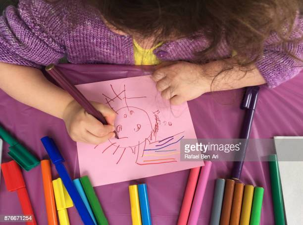 Little girl painting with colouring pens