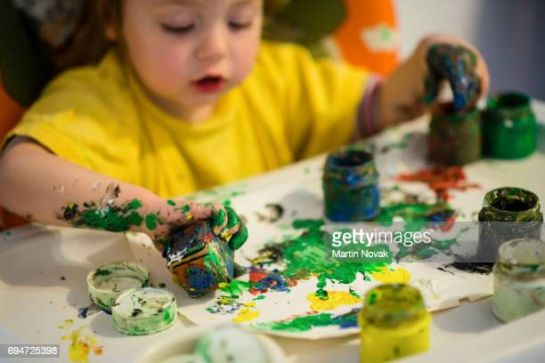 Little girl painting with fingers