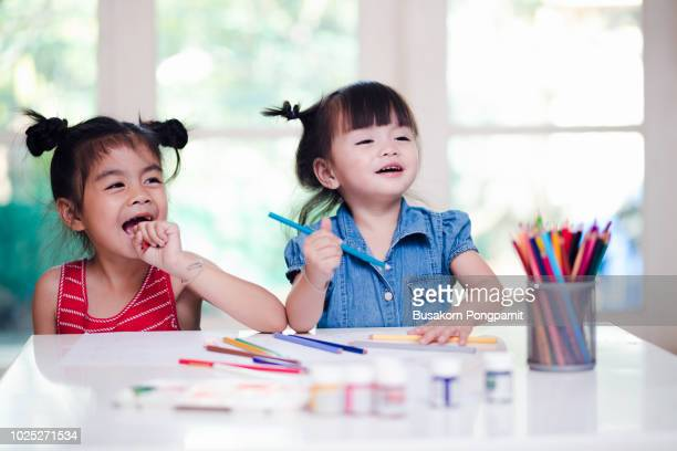 little girl painting with paintbrush and colorful paints on desk background - very young thai girls stock photos and pictures