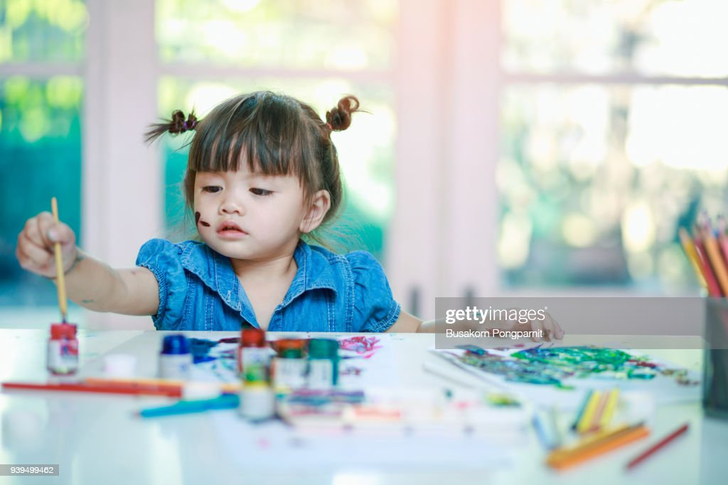 little girl painting with paintbrush and colorful paints on desk background : Stock Photo