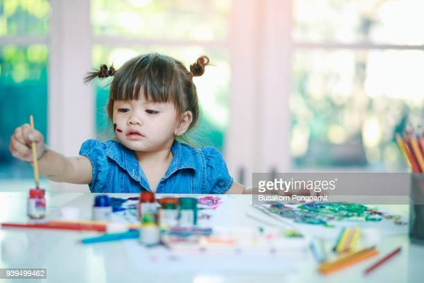 little girl painting with paintbrush and colorful paints on desk background