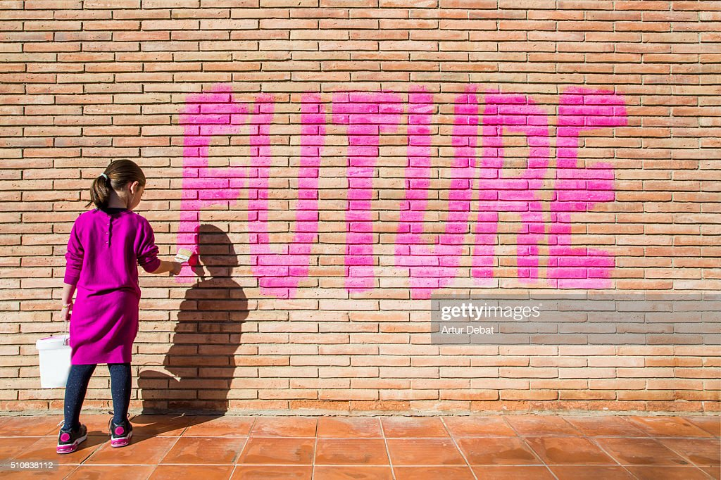 Little girl painting with pink colors the future word in a brick wall, a protest action claiming for future to the new generations. : Foto de stock