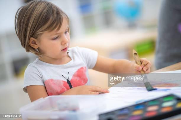 kleine meisje schilderen met waterkleuren - linkshandig stockfoto's en -beelden