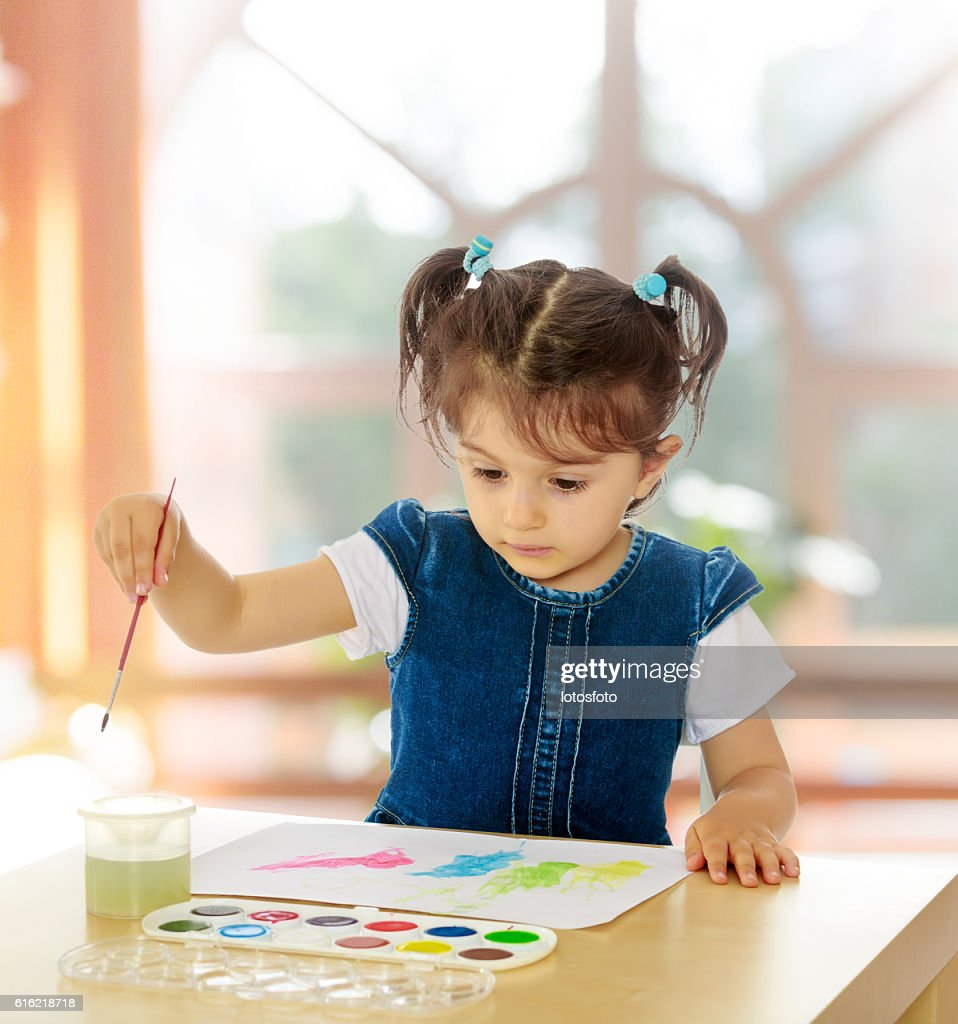 Little girl paints with watercolors at the table. : Stock-Foto
