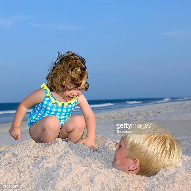 A little girl pats on the sand where a boy is buried up to his head