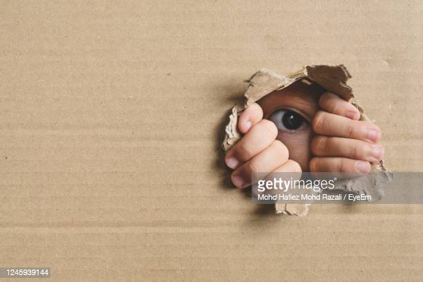 little girl peeking from a hole on cardboard box. concept of a human trafficking and curiosity - human trafficking stock pictures, royalty-free photos & images