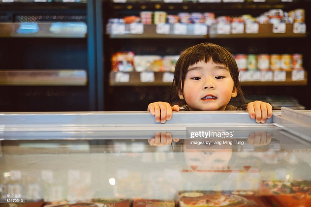 Lovely little girl standing on tiptoe peeking into the freezer curiously in the supermarket.
