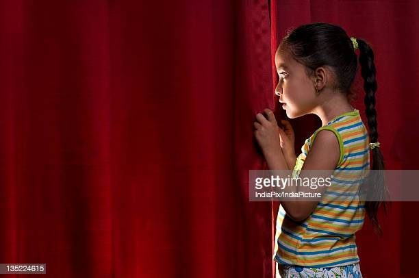 Little girl peeking out from behind the curtain