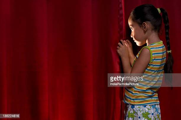 little girl peeking out from behind the curtain - stage curtain stock pictures, royalty-free photos & images