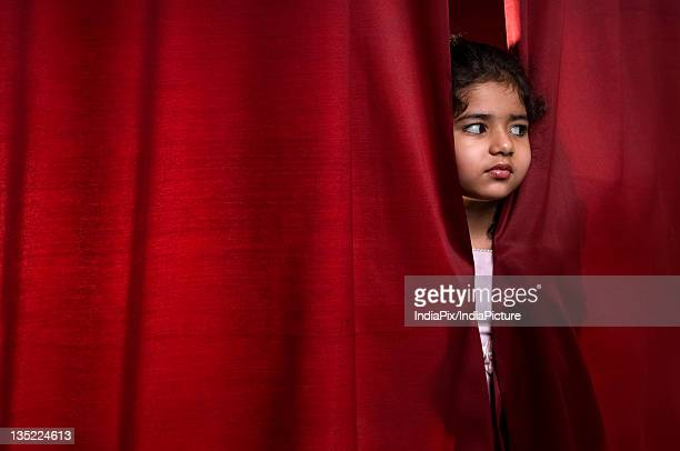 little girl peeking out from the curtain - あがり症 ストックフォトと画像