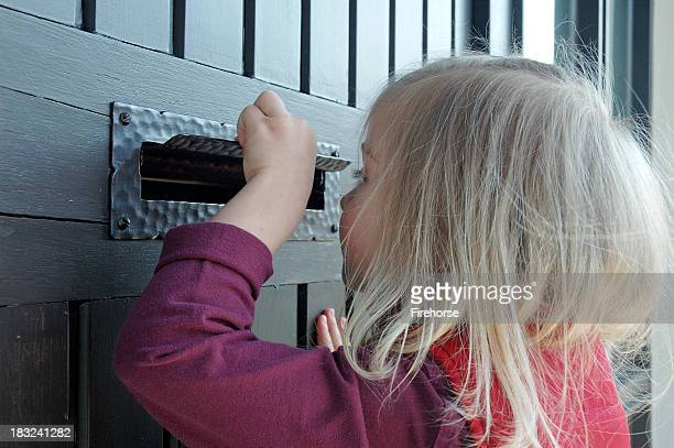 A little girl peeking through a mail slot on a house