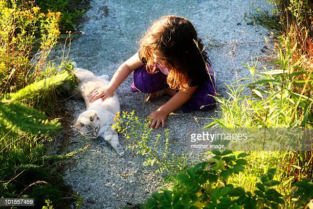 Little girl petting her cat outdoors
