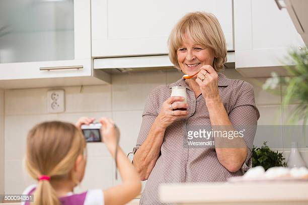 Little girl photographing her grandmother in kitchen