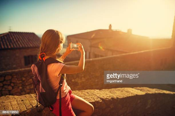 little girl photographing sunset over beautiful village in tuscany - camera girls stock photos and pictures