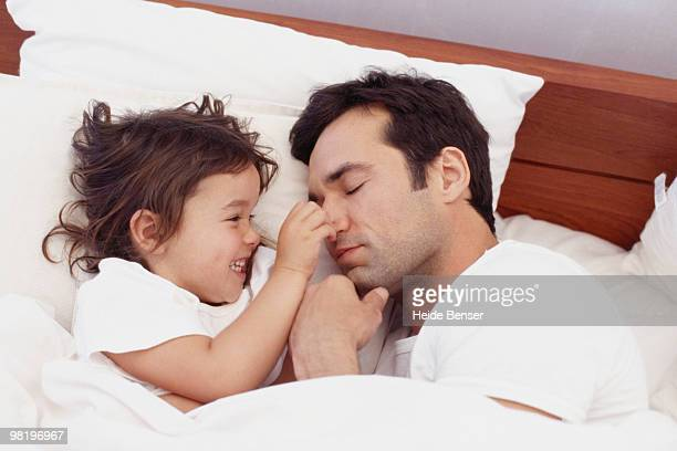 Little girl pinches her sleeping father's nose