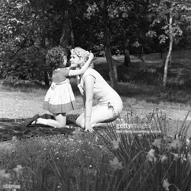 A little girl placing a daisy chain on the head of a woman Wimbledon Common London 16th May 1962