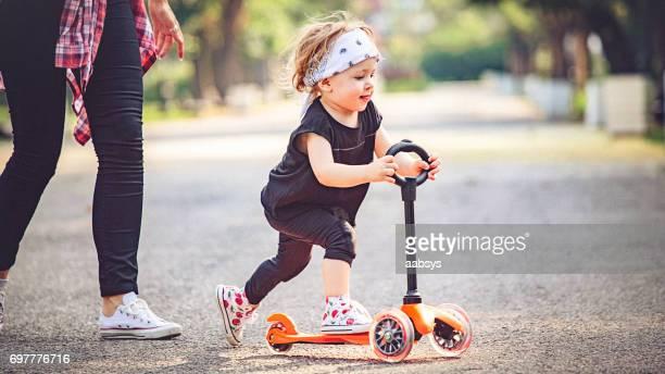 Kleine Mädchen spielen im Park, Push-Scooter fahren.