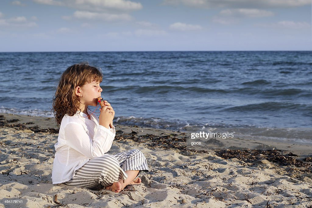 little girl play pan pipe on beach : Stock Photo