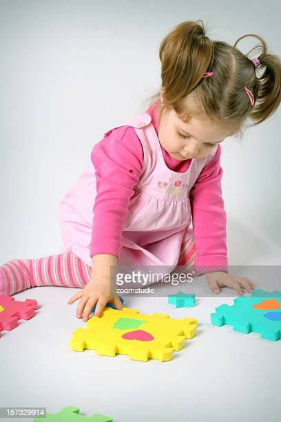 Little girl play with puzzles