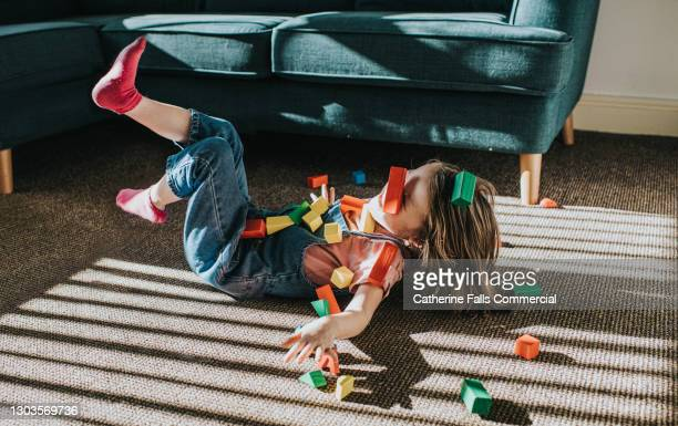little girl playfully falls backwards as colourful wooden blocks scatter - freedom stock pictures, royalty-free photos & images