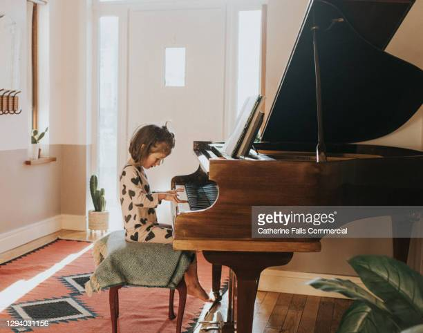 little girl playing a grand piano in a domestic environment - human finger stock pictures, royalty-free photos & images