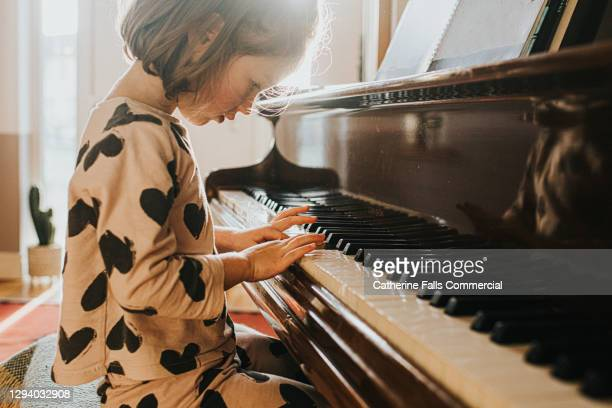 little girl playing a grand piano - human finger stock pictures, royalty-free photos & images