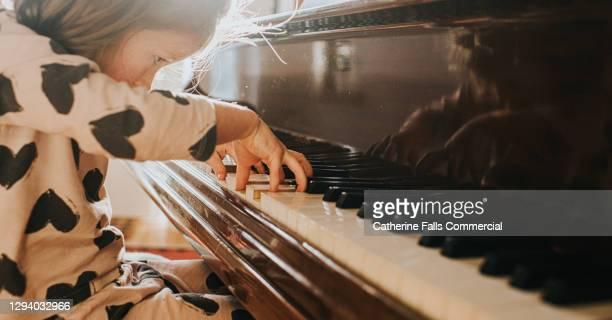 little girl playing a grand piano - wonderkind stockfoto's en -beelden