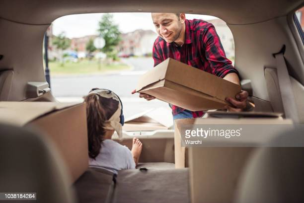 little girl playing and listening to music in the trunk of the car while her father is loading moving boxes - car trunk stock pictures, royalty-free photos & images