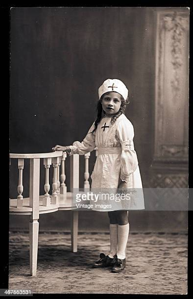 A little girl playing at being a nurse circa 1890