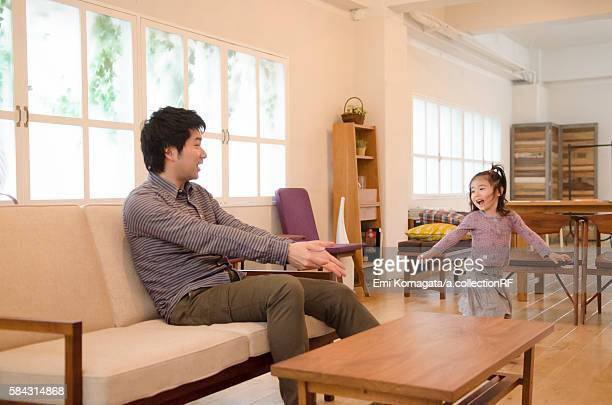 Little girl playing at living room, with her father sitting on sofa