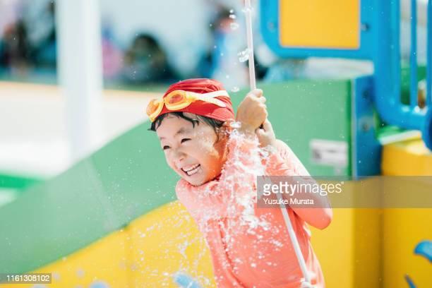little girl playing at the pool - loslassen aktivitäten und sport stock-fotos und bilder