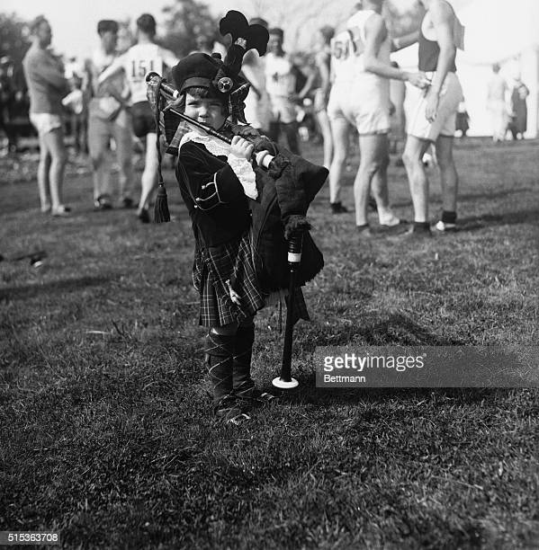 Little Girl Playing Bagpipes, football players in background. Boston, Massachusetts, USA. August 04, 1925