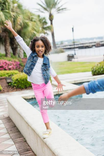 Little girl playing, balancing on side of fountain