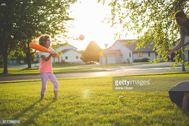 little girl playing baseball with her father - batting sports activity stock pictures, royalty-free photos & images