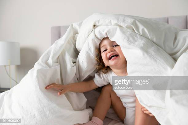 little girl playing bed - bedding stock pictures, royalty-free photos & images