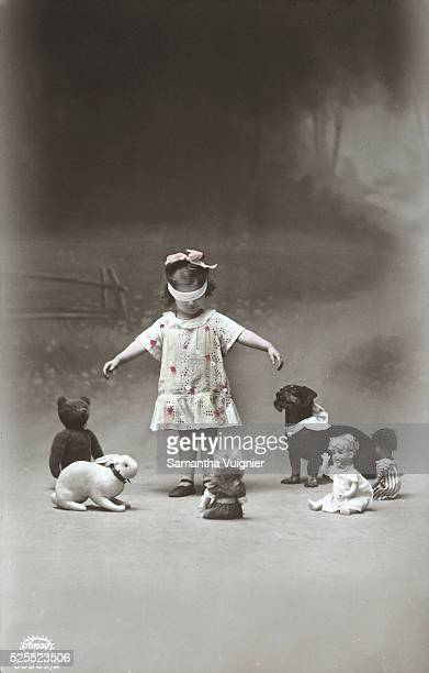 Little girl playing Blind Man's Bluff with her dolls stuffed animals and a dachshund dog