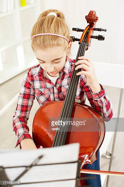 Little Girl Playing Cello at home.