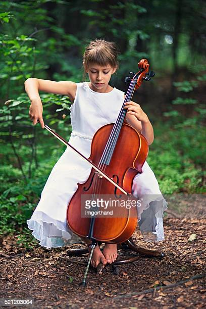 Little girl playing cello in forest