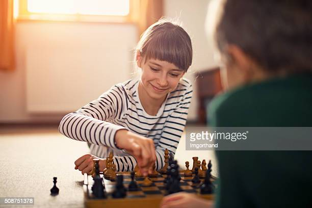 Little girl playing chess with her brother
