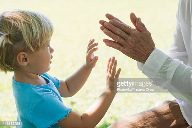 Little girl playing clapping game with grandmother, cropped