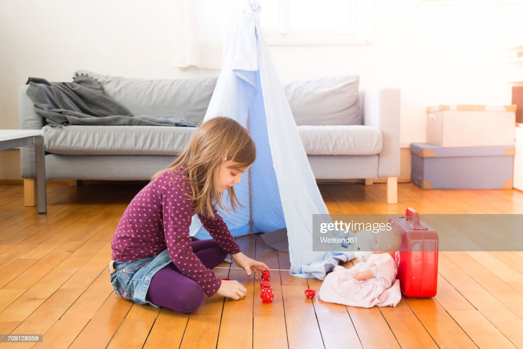 Little girl playing coffee party with her toys on the floor at home : Stock Photo