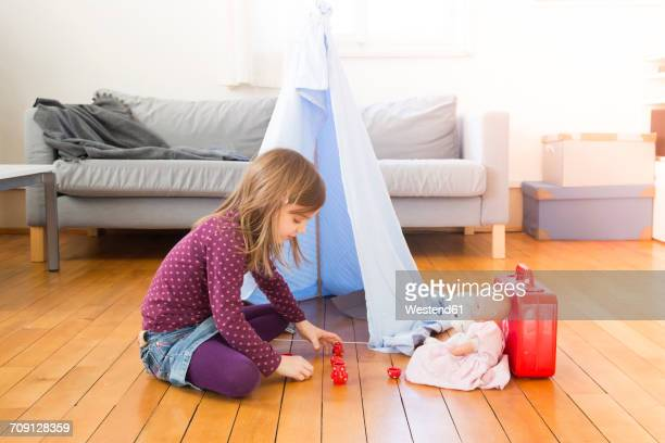 Little girl playing coffee party with her toys on the floor at home