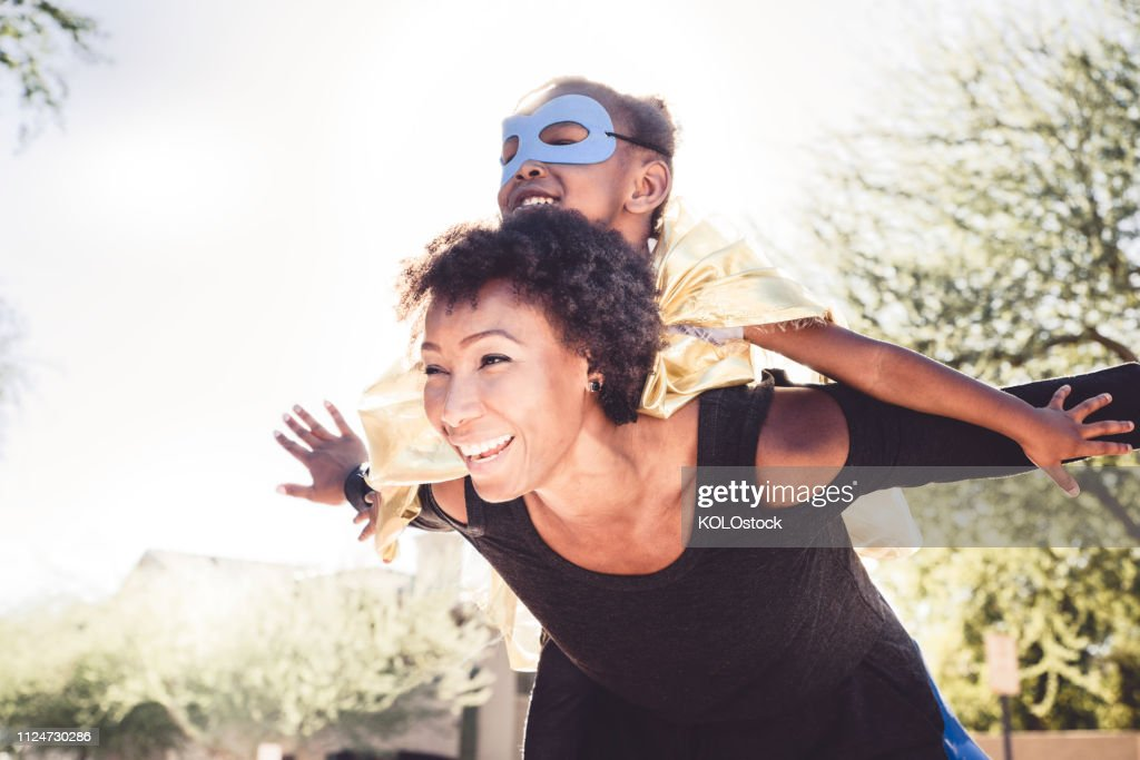 Little girl playing dressing up with her mother : Stock Photo