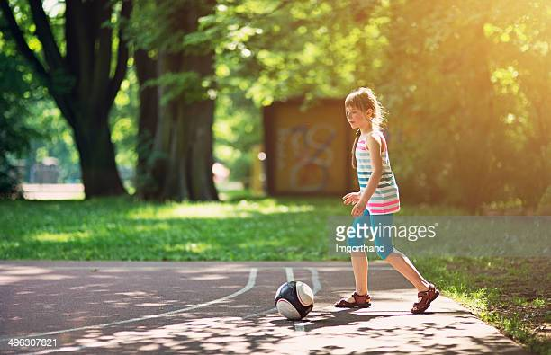 Little girl playing football in the park