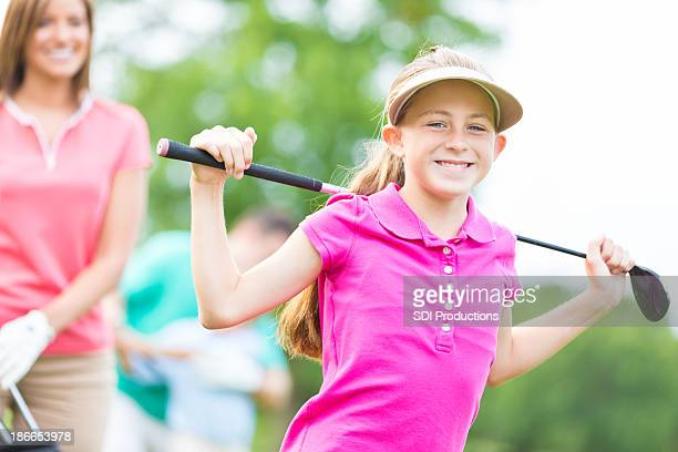 Little girl playing golf with family on country club course