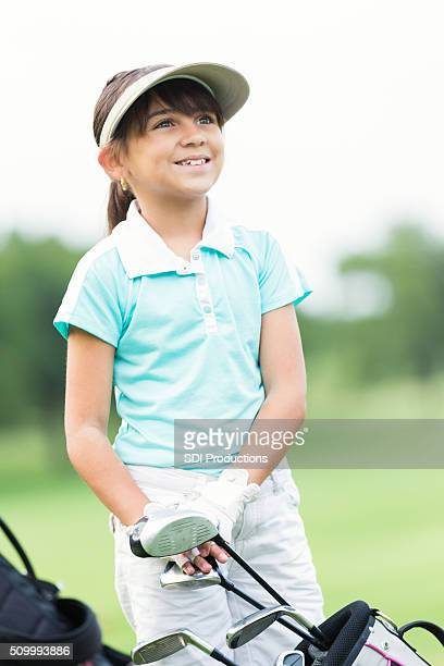 Little girl playing golf with family