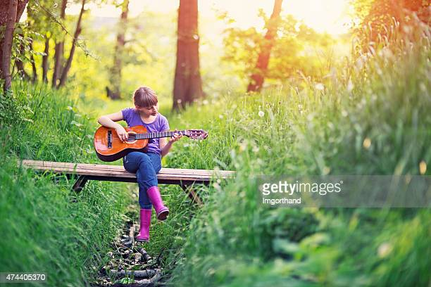 Little girl playing guitar on little bridge in forest