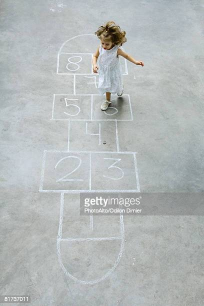 Little girl playing hopscotch, high angle view