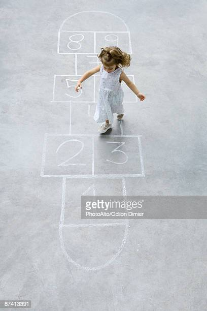 little girl playing hopscotch, high angle view - hopscotch stock pictures, royalty-free photos & images