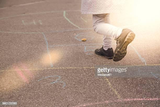 Little girl playing hopscotch
